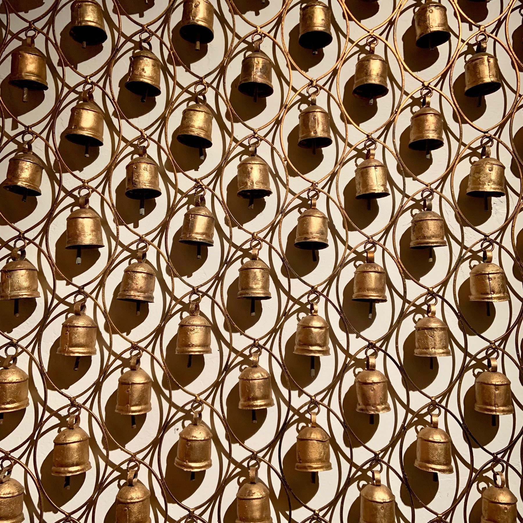 many bells hanging from a frame