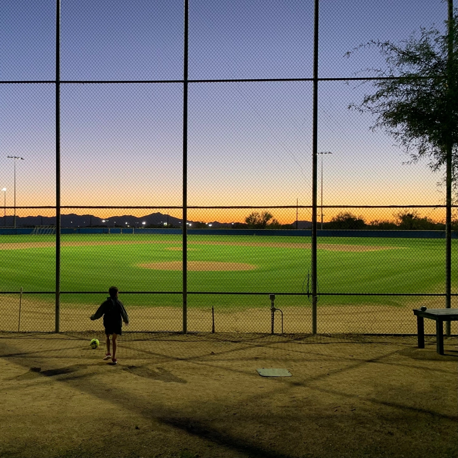 child with ball outside a baseball field at sunset